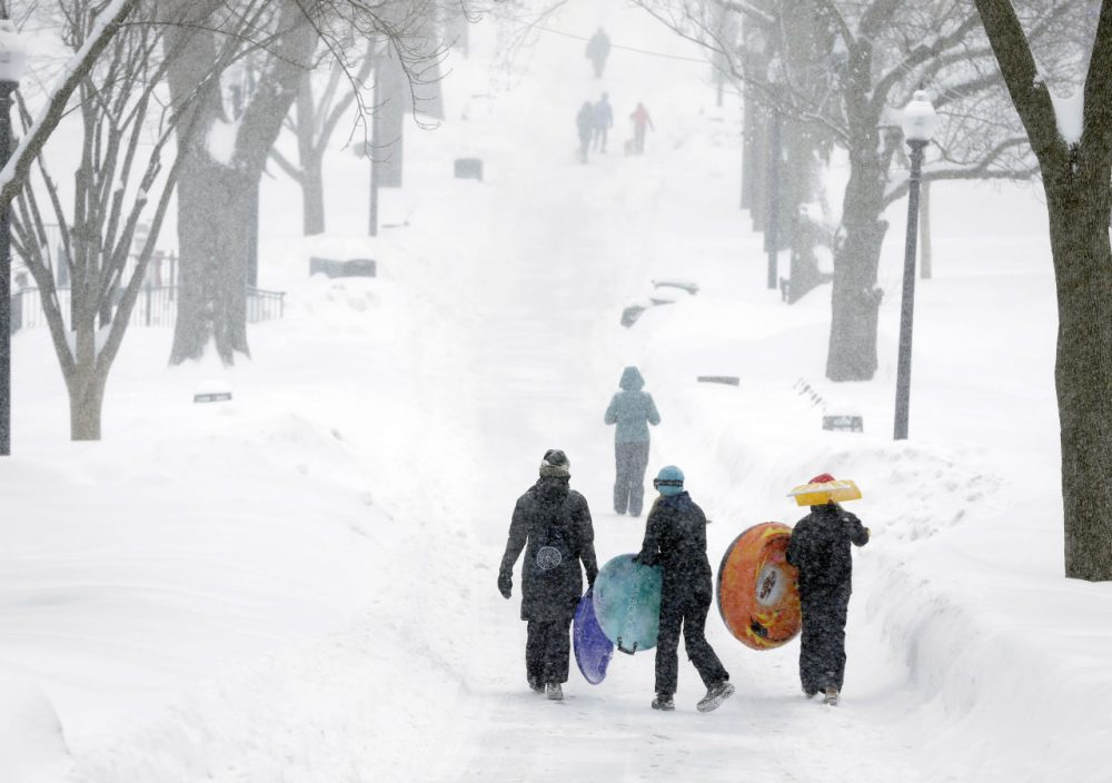 People carry their sleds at the Boston Common last week during the third major winter storm this year. (Steven Senne/AP)