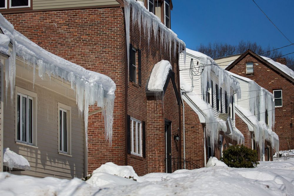 Huge banks of snow hindered many potential homebuyers from getting to know neighborhoods and finding parking spaces around homes for sale. In this photo taken last month, icicles hang from homes buried in snow along Itasca Street in Mattapan. (Jesse Costa/WBUR)