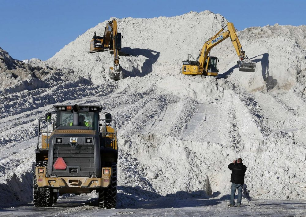 "Heavy equipment worked on a mound of snow that had been cleared from city streets at a ""snow farm"" in Boston, Monday, Feb. 16. (Michael Dwyer/AP)"