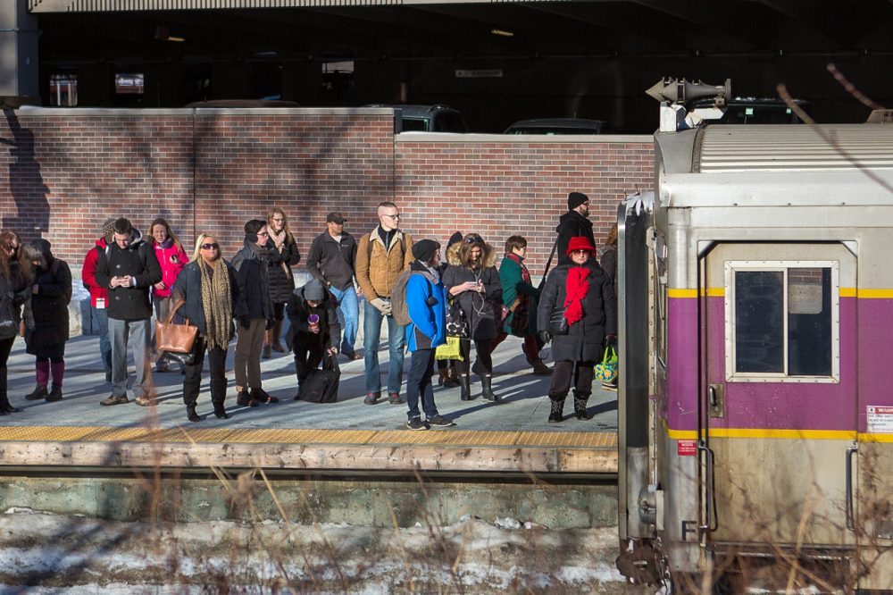Commuters wait on the platform in Salem as an MBTA commuter rail train arrives in early March. (Jesse Costa/WBUR)