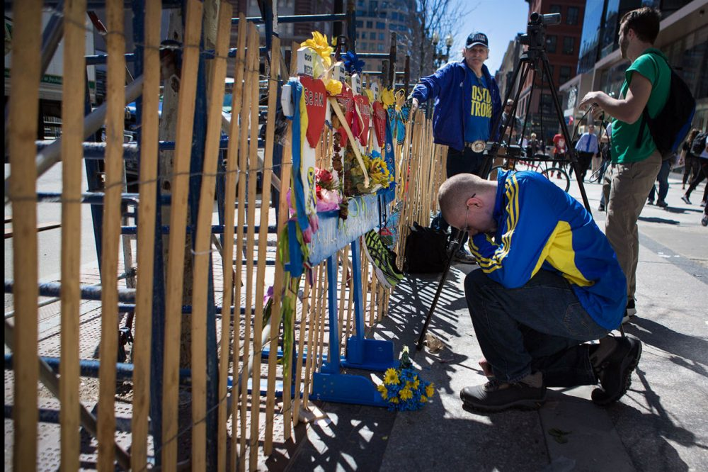 A man stops and prays for the victims of the Boston Marathon bombing Wednesday at a small memorial near the finish line on Boylston Street.(Jesse Costa/WBUR)