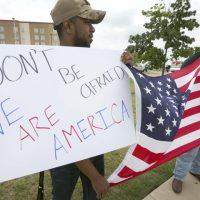 Joseph Offutt, left, and Raheem Peters hold a sign and a U.S. flag across the street from the Curtis Culwell Center, Tuesday, May 5, 2015, in Garland, Texas. A man, whose social media presence was being scrutinized by federal authorities, was one of two suspects killed in the Sunday shooting at this location that hosted a cartoon contest featuring images of the Muslim Prophet Muhammad. (AP)