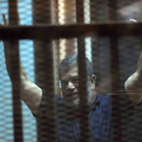 Ousted Egyptian President Mohammed Morsi raises his hands as he sits behind glass in a courtroom, in a converted lecture hall in the national police academy in an eastern Cairo suburb, Egypt, Saturday, May 16, 2015. (AP)