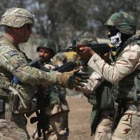 A U.S. Army trainer (L), instructs Iraqi Army recruits at a military base on April 12, 2015 in Taji, Iraq. Members of the U.S. Army's 5-73 CAV, 3BCT, 82nd Airborne Division are teaching members of the newly-formed 15th Division of the Iraqi Army, as the Iraqi government launches offensives to try to recover territory lost to ISIS last year. (John Moore/Getty Images)