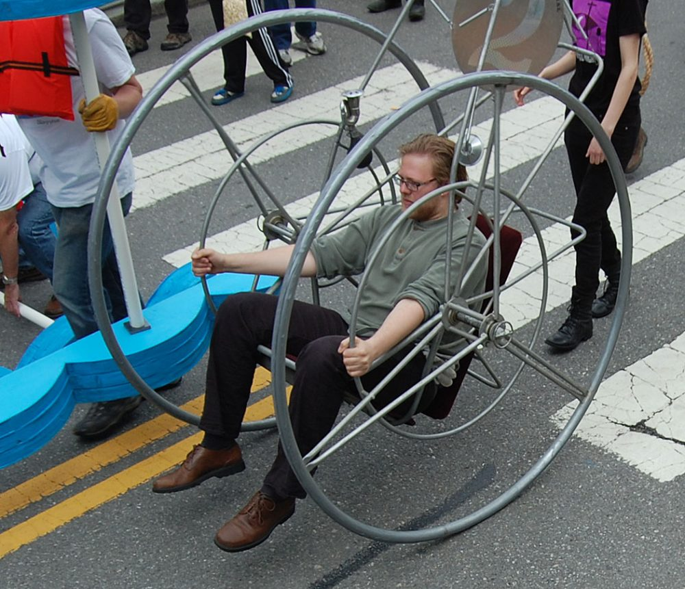 """Wheel #2"" was made by Bill Wainwright for the 1982 sculpture race and will be entering the permanent collection of the MIT Museum on Monday, race organizer Christian Herold said. His nephew, James Herold, who piloted it today, said, ""It's kind of like a cantilevered wheelchair with just two wheels. You have these smaller hand wheels that you move to go. It's got a 0-degree turning radius. You can get up to some pretty significant speeds in this but the faster you go, the less control you have so you really don't want to do that."" (Greg Cook/WBUR)"