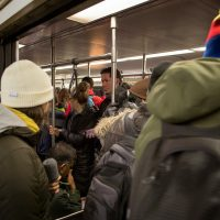Passengers squeeze aboard a Red Line train at the Porter Square MBTA station. (Robin Lubbock/WBUR)