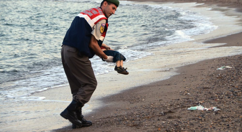 A Turkish paramilitary police officer carries the body of 3-year-old Aylan Kurdi, found washed ashore near the Turkish resort of Bodrum early Wednesday, Sept. 2, 2015. The boats carrying the boy's family to the Greek island of Kos capsized. His 5-year-old brother and mother also lost their lives. (AP)