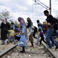 People pass railway tracks as they approach the southern Macedonian town of Gevgelija,Tuesday, Sept. 8, 2015. Hundred of thousands migrants and refugees trying to reach the heart of Europe via Turkey, Greece, the Balkans and Hungary have faced dangers, difficulties and delays on every link of the journey.  (AP)