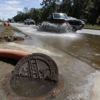 A manhole begins to spill over with floodwaters as high tide approaches at Dorchester Road at Sawmill Branch Canal in Summerville, S.C., Thursday, Oct. 8, 2015.  (AP)