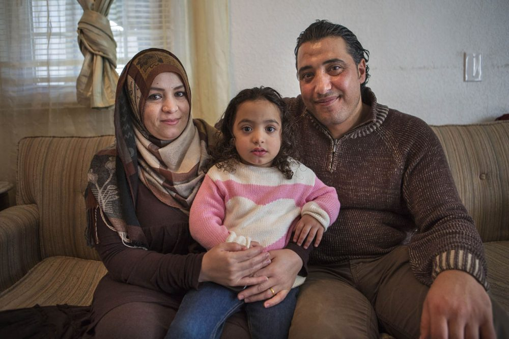 A year ago, Zenab Al-Nassar, left, and her husband, Zid, who are Syrian, were resettled as refugees in western Massachusetts. They're seen here with a daughter, Tuka, in their home in Westfield. (Jesse Costa/WBUR)