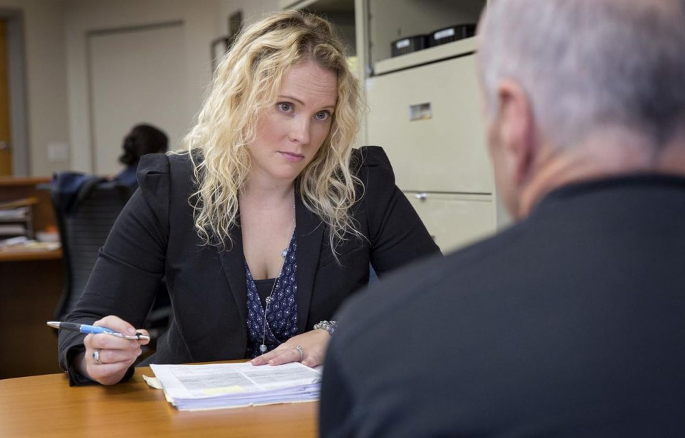 Eve Elliott, a staff attorney at Veterans Legal Services, talks with a veteran. (Robin Lubbock/WBUR)
