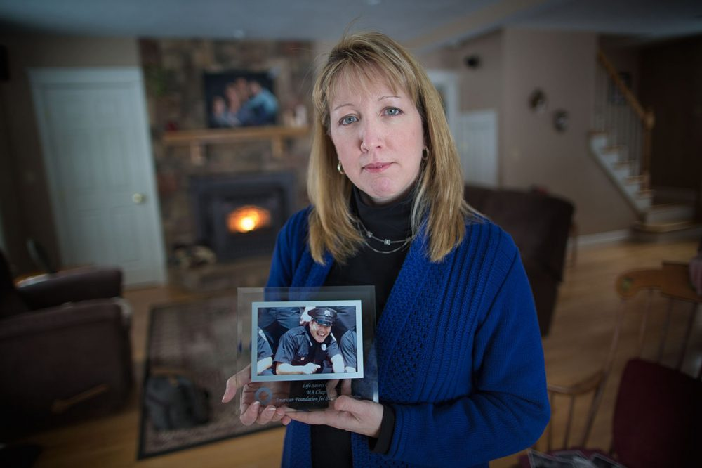 Justine Barnes holds a photo of her brother, Luke LaCaire, who died by suicide. (Jesse Costa/WBUR)