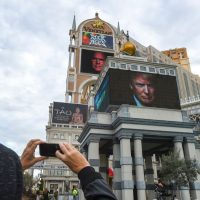 A tourist takes a picture of advertisements for the fifth of the season GOP presidential debate, which will be hosted by CNN on Tuesday, Dec. 15 in Las Vegas. (Robyn Beck//AFP/Getty Images)