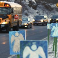 "In this Jan. 3, 2013 photo, a bus traveling from Newtown, Conn. stops near 26 angel signs posted along the roadside in Monroe, Conn., on the first day of classes for Sandy Hook Elementary School students since the Dec. 14, 2012, shooting. The massacre in Newtown, in which a mentally troubled young man killed 26 children and teachers, served as a rallying cry for gun-control advocates across the nation. But in the three years since, many states have moved in the opposite direction, embracing the National Rifle Association's axiom that more ""good guys with guns"" are needed to deter mass shootings. (Jessica Hill/AP)"