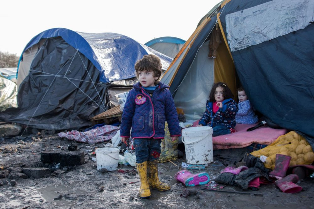 Children of Kurdish migrants gather outside a tent at the Grande Synthe migrant camp near Dunkerque in northern France on December 23, 2015. More than 2,000 migrants, mostly Iraqis and Kurds, live in the camp. (Denis Charlet/AFP/Getty Images)