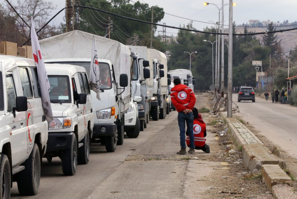 A convoy of aid from the International Committee of the Red Cross (ICRC) waits on the outskirts of the besieged rebel-held Syrian town of Madaya, on January 11, 2016.  Dozens of aid trucks headed to Madaya, where more than two dozen people are reported to have starved to death, after an outpouring of international concern and condemnation over the dire conditions in the town, where some 42,000 people are living under a government siege.  (Louai Beshara/AFP/Getty Images)
