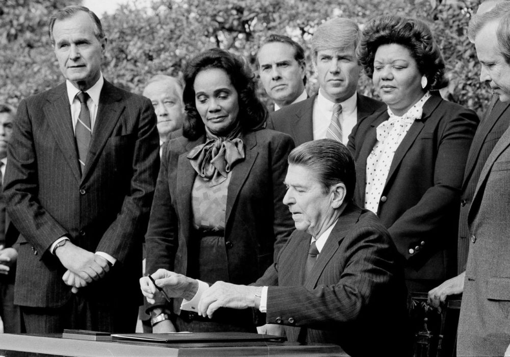 Former President Ronald Reagan signs the bill making Martin Luther King Jr.'s birthday into a national holiday, as Coretta Scott King watches on Nov. 2, 1983, in Washington. (Barry Thumma/AP)