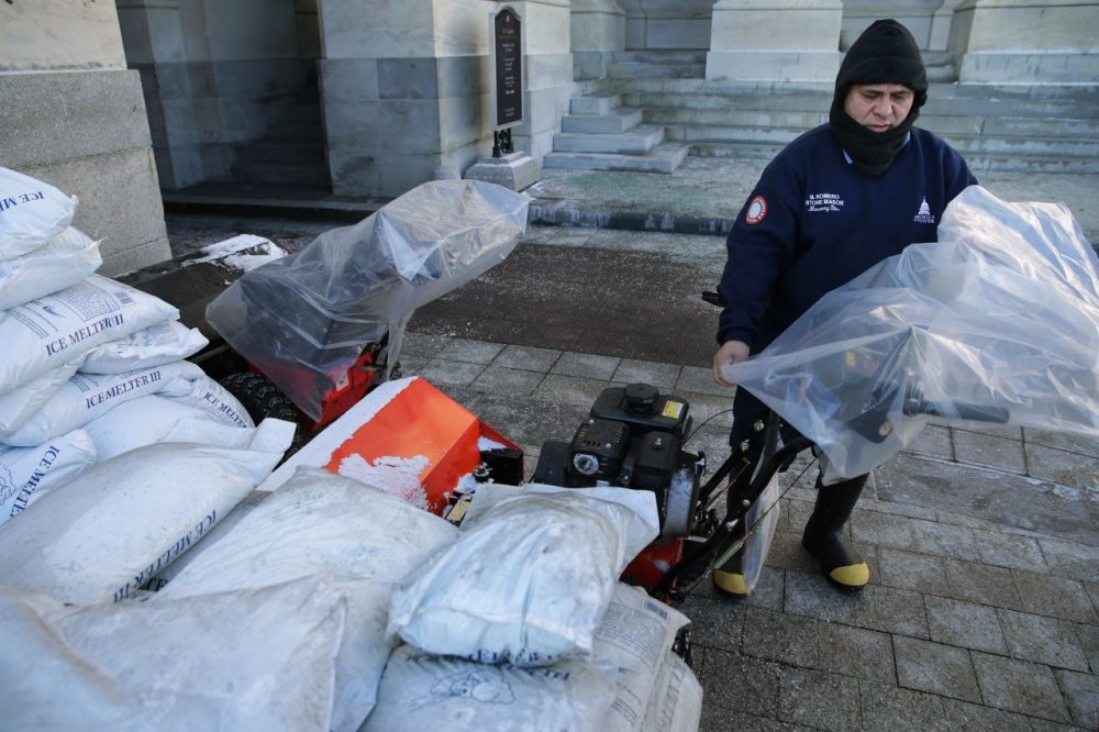 Surrounded by bags of ice-melting salt, stone mason Medaro Romero covers gas powered snow sweepers in plastic bags in preparation for a coming winter storm outside the U.S. Capitol January 21, 2016 in Washington, DC. One inch of snowfall delayed school openings in the greater Washington, DC, area on Thursday as people along the Easter Seaboard prepare for a blizzard to arrive within the next 24 hours. (Chip Somodevilla/Getty Images)