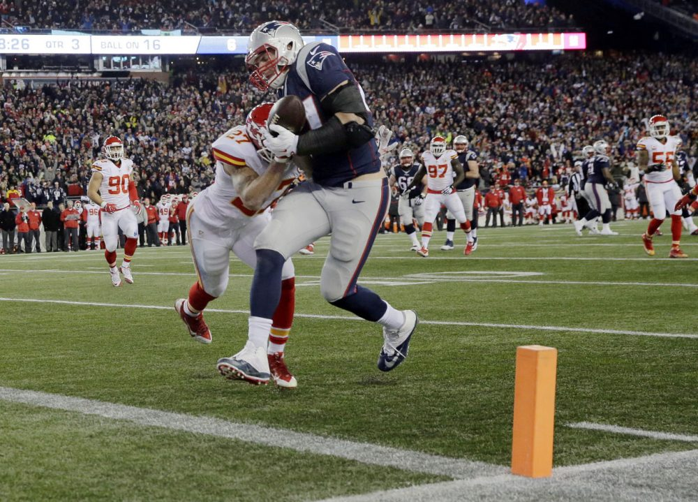 Patriots tight end Rob Gronkowski catches a pass for a touchdown ahead of Chiefs defensive back Tyvon Branch in the divisional playoff on Saturday. (Charles Krupa/AP)