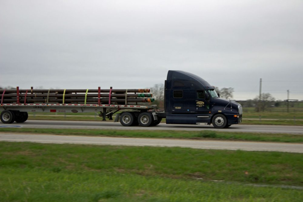 A truck on I-10 in Colorado County, Texas, hauls drilling pipe in 2013, (Dave Fehling/Houston Public Media)