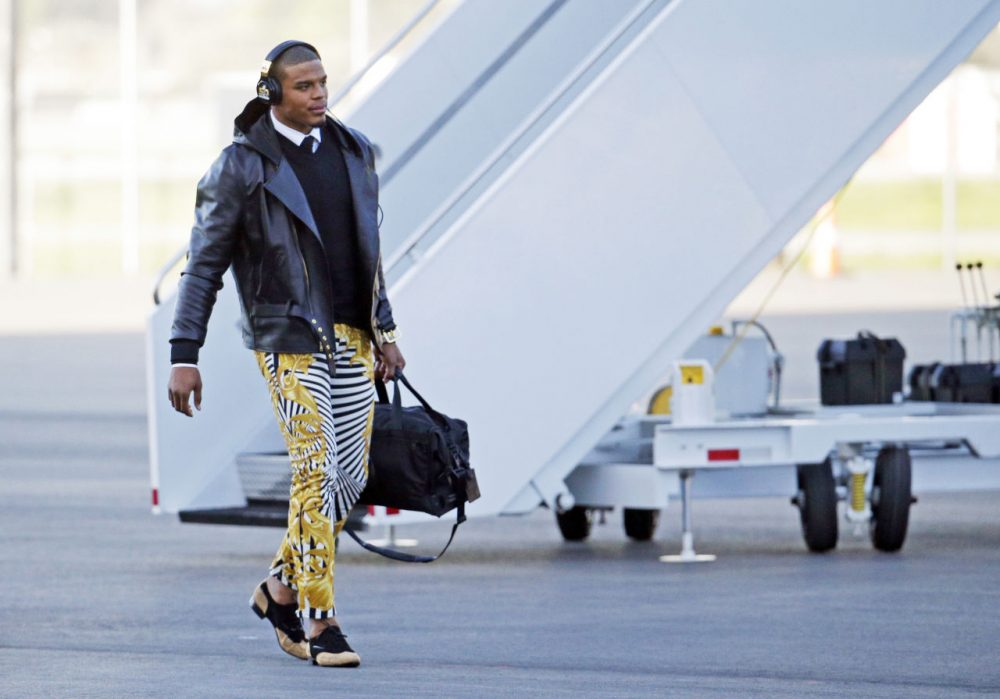 In this Jan. 31, 2016 photo, Carolina Panthers quarterback Cam Newton gets off the plane at the Mineta San Jose International Airport in San Jose, Calif.  The Panthers play the Denver Broncos on Sunday, Feb. 7, 2015, in Super Bowl 50. Newton was snapped Sunday in the zebra stripe, gold swirl rocker pants immediately setting social media and TV talking heads into a frenzy. (Charlie Riedel/AP)