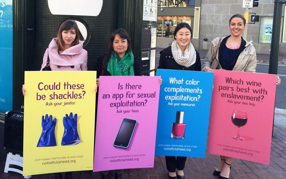 Public policy fellows with San Francisco's Department on the Status of Women hold mockups of anti-trafficking billboards. (Tara Siler/KQED)