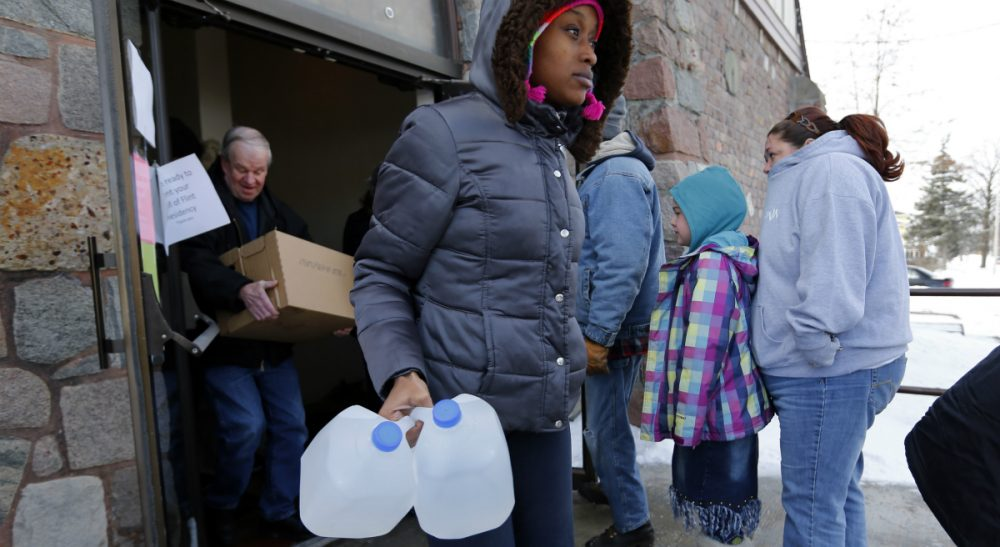 In this Tuesday, Feb. 3, 2015 photo, a Flint resident carries free water being distributed at the Lincoln Park United Methodist Church in Flint, Mich. Since the financially struggling city broke away from the Detroit water system in April 2014, residents have been unhappy with the smell, taste and appearance of water from the city's river as they await the completion of a pipe to Lake Huron. They also have raised health concerns, reporting rashes, hair loss and other problems. (Paul Sancya/AP)
