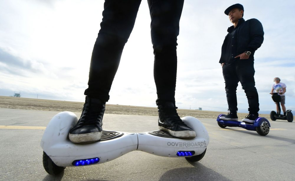 People ride their hoverboards on the Venice Beach Boardwalk, California on December 10, 2015. These so-called hoverboards, or self-balancing electric scooters, are surging in popularity in the first season where they have been available at relatively affordable prices -- as low as $300 for some models. (Frederic J. Brown/AFP/Getty Images)