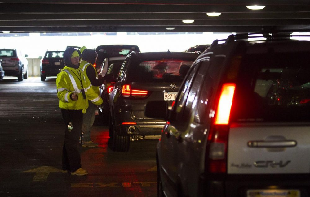 Central Parking Garage attendants guide and register customers as they box in other cars already parked in assigned parking spots. The cars will be left where they are stopped until cars parked in assigned spots leave. (Jesse Costa/WBUR)