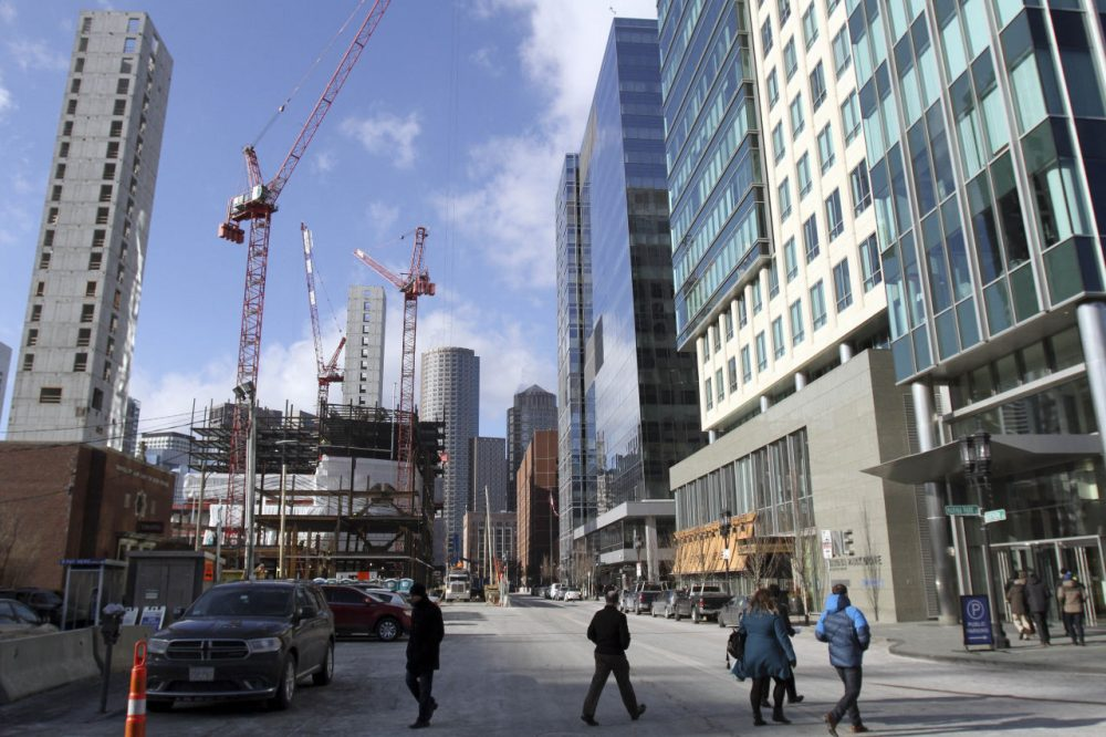 Construction takes place on two buildings, left, adjacent to three recently built buildings, right, in Boston's Seaport District. (Bill Sikes/AP)