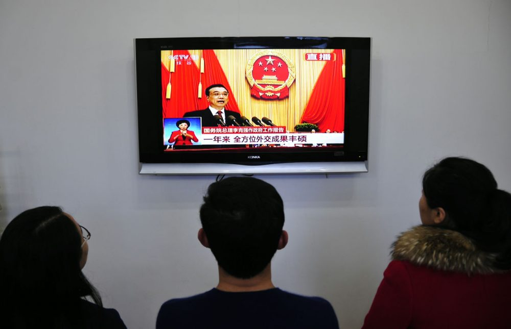 Chinese people watch live television coverage at a conference room in Yantai, east China's Shandong province as Chinese Premier Li Keqiang delivers his report during the opening ceremony of the National People's Congress in the Great Hall of the People in Beijing on March 5, 2016. (STR/AFP/Getty Images)