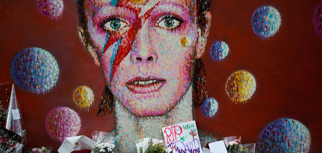 Tributes lie beneath a mural of British singer David Bowie by artist Jimmy C in Brixton, south London on Jan. 12, 2016. (Matt Dunham/AP)