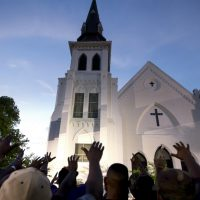 "Mark Edington: ""We don't need more weapons to make ourselves safer. We need more places of pilgrimage. And we need to go, not as tourists, but as pilgrims — people willing to be changed."" Pictured: A crowd of people in prayer outside the Emanuel AME Church, Friday, June 19, 2015. Nine people were shot to death at the church two days prior. (AP Photo/Stephen B. Morton)"
