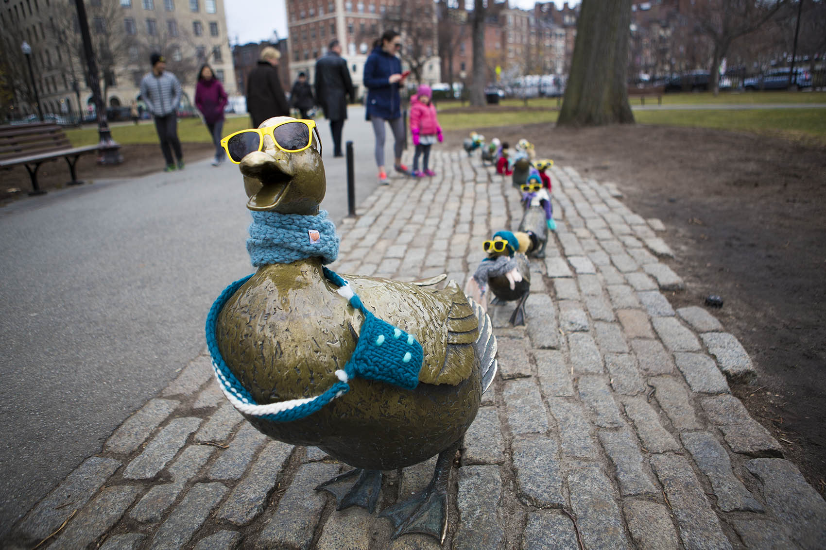 Nancy Schon's Make Way For Ducklings Statues dreassed in winter clothing in The Public Gardens. (Jesse Costa/WBUR)