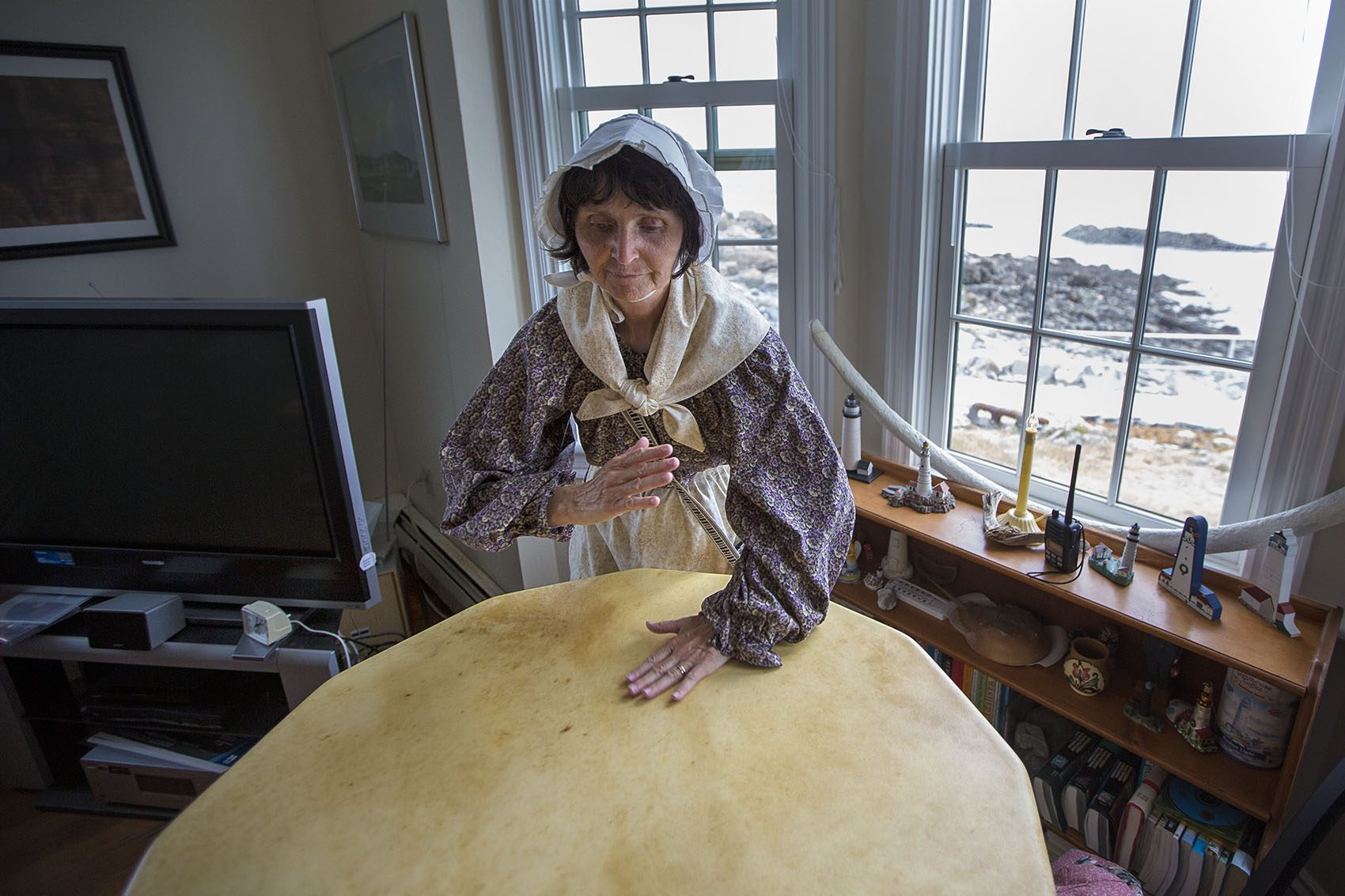 Sally Snowman plays her handmade drum made with buffalo skin. (Jesse Costa/WBUR)