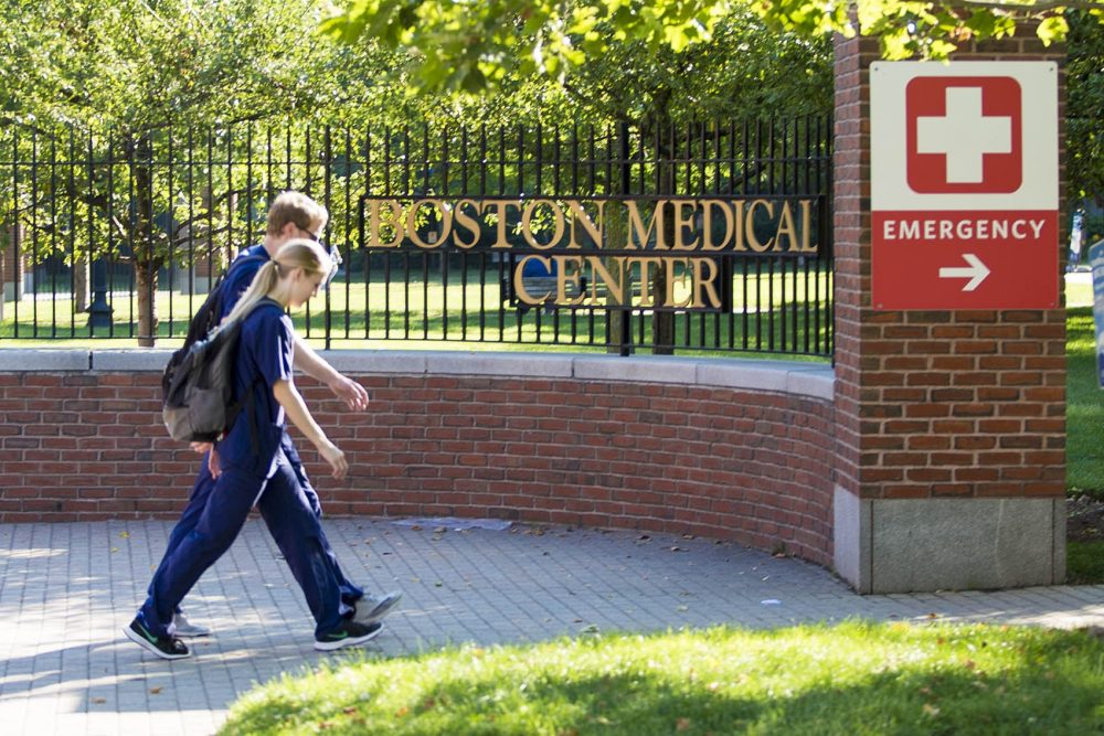 Medical personnel enter Boston Medical Center through the emergency entrance gate on Harrison Avenue. (Jesse Costa/WBUR)