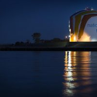 Corita Kent's rainbow gas tank reflects in the Dorchester Bay at night. (Robin Lubbock/WBUR)