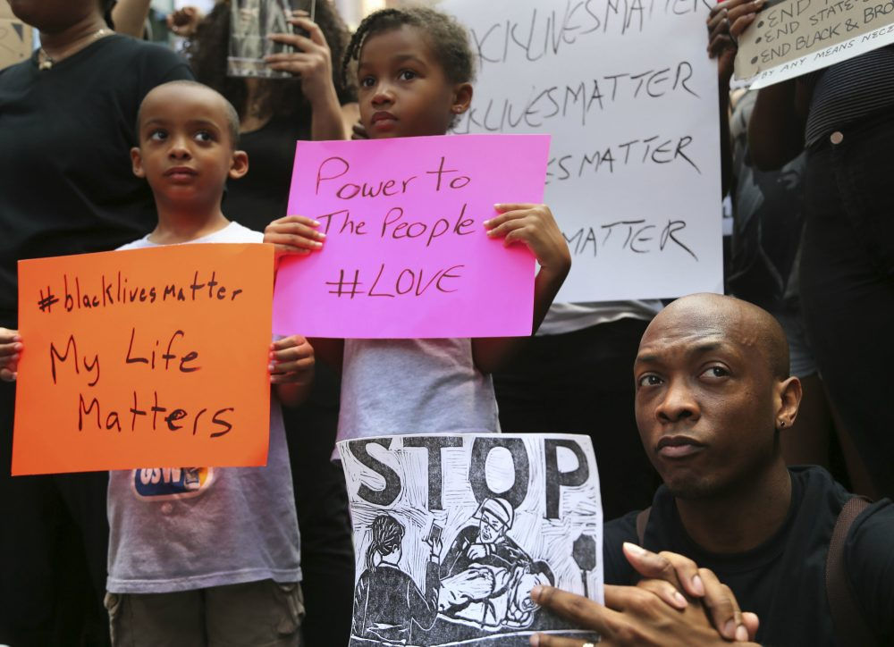 Jashaun Sadler, right, and his twins Malik, left, and Jazlin Sadler listen to speakers during a Black Lives Matter demonstration in New York, Sunday, July 10, 2016. A crowd of about 300 people protested against the shootings of black men by police officers. (Seth Wenig/AP)