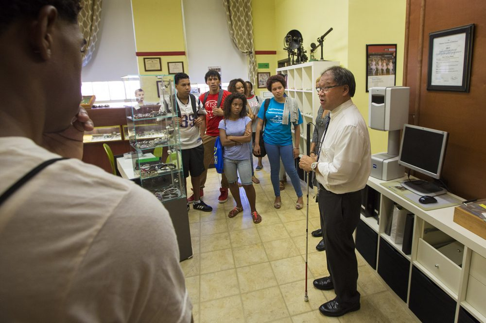 Professor Blair Wong speaks with a group of prospective students interested in the opticians program at Benjamin Franklin Institute of Technology. (Jesse Costa/WBUR)