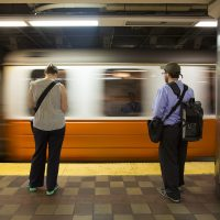 Commuters wait on the platform as an Orange Line train enters Downtown Crossing station. (Jesse Costa/WBUR)
