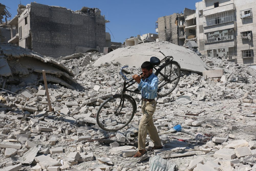 A Syrian man carrying a bicycle makes his way through the rubble of destroyed buildings following a reported air strike on the rebel-held Salihin neighbourhood of the northern city of Aleppo, on Sept. 11, 2016. (Ameer Alhabi/AFP/Getty Images)
