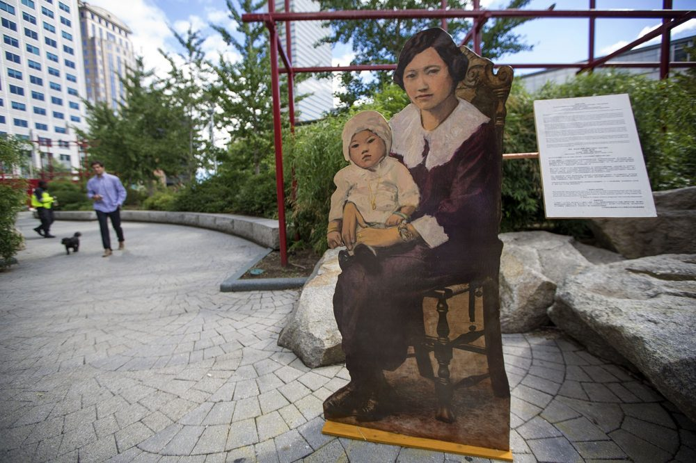 """Mother and Baby"" sits at the edge of Chinatown Park, one of artist Wen-Ti Tsen's life-size portraits of residents illustrating the neighborhood's long history. (Jesse Costa/WBUR)"