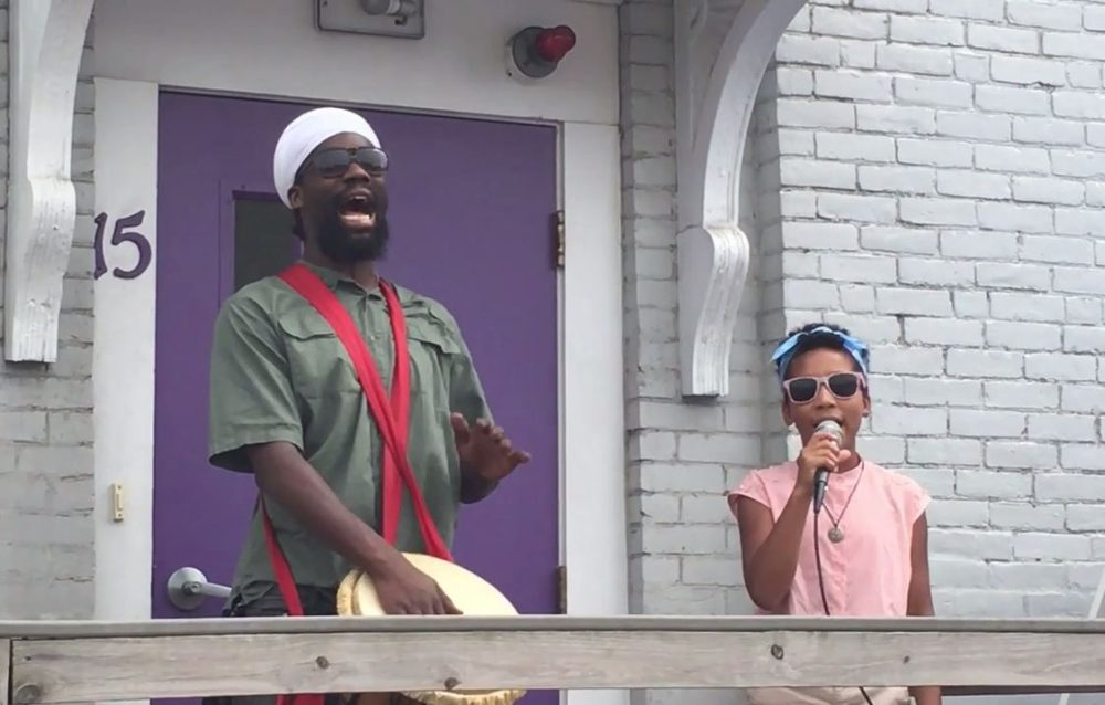 "Inari Jade Higgins Barrett, right, sings ""Fly Like a Dove"" at the Louis D. Brown Peace Institute accompanied by her father, Toussaint Liberator. (Vimeo screenshot)"