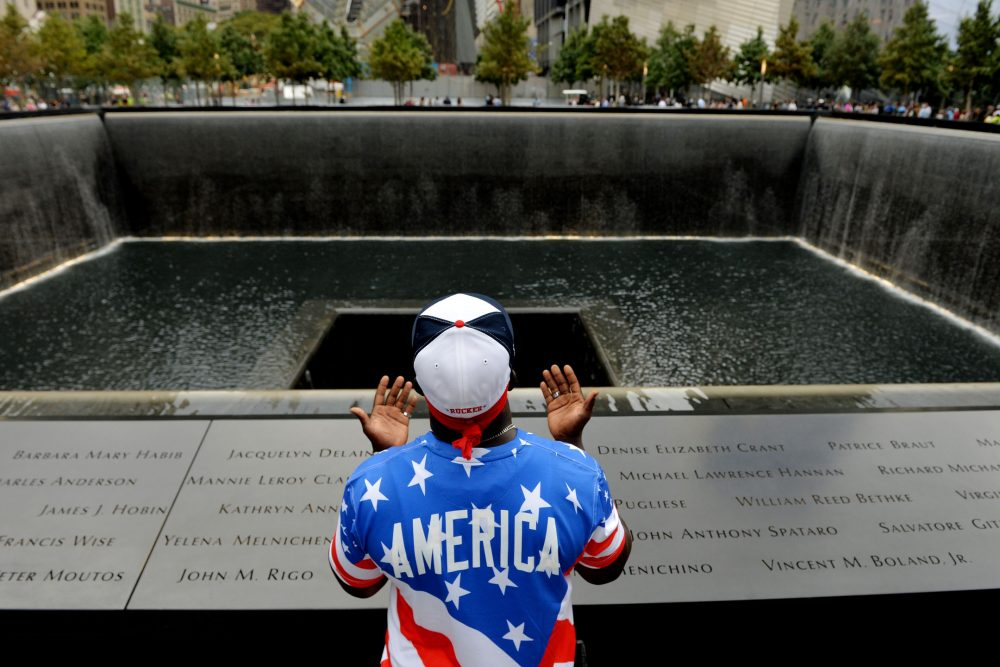 Albert Biatta, of Queens, prays while standing front of the inscribed name of his uncle Antoine Biatta at the edge of the North Pool during memorial observances on the anniversary of the 9/11 terror attacks on the World Trade Center (Justin Lane/AP File)