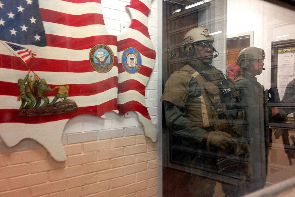 Armed state troopers are seen through a window as they accompany Alabama Gov. Robert Bentley inside Holman prison in Atmore, Ala., on Tuesday, March 15, 2016. (Melissa Brown/AP)