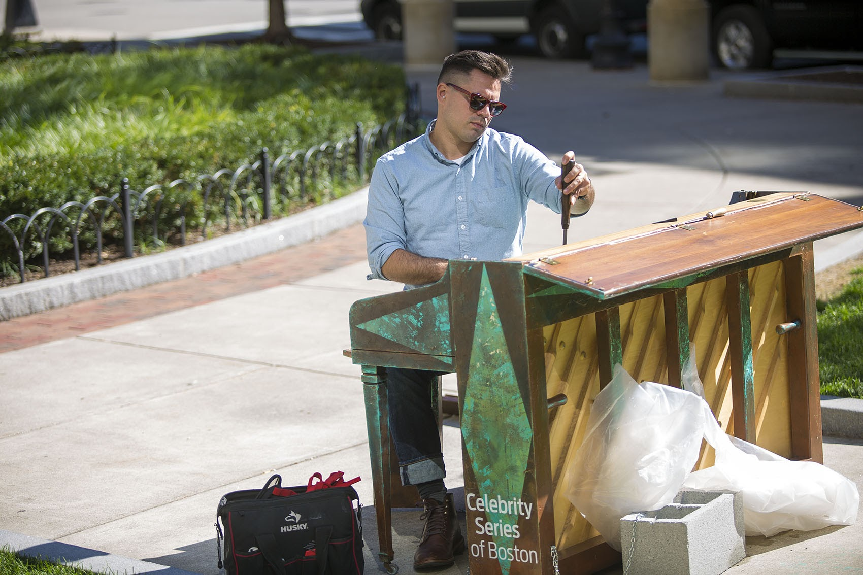 "Piano technician Michael Wilson tunes one of the ""Play Me, I'm Yours"" pianos, this one in Statler Park near the Park Plaza Hotel in Boston. (Jesse Costa/WBUR)"