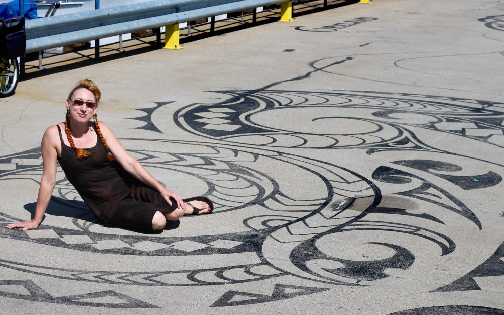 "Artist Liz LaManche sits on her ""Connected by Sea"" installation on the dock of the East Boston Shipyard. (Amy Gorel for WBUR)"