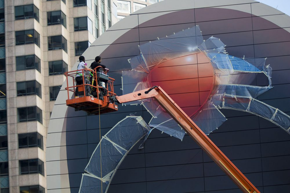 Mehdi Ghadyanloo and his assistant, Henry Kunkel, examine the balloon at the top of the mural. (Jesse Costa/WBUR)