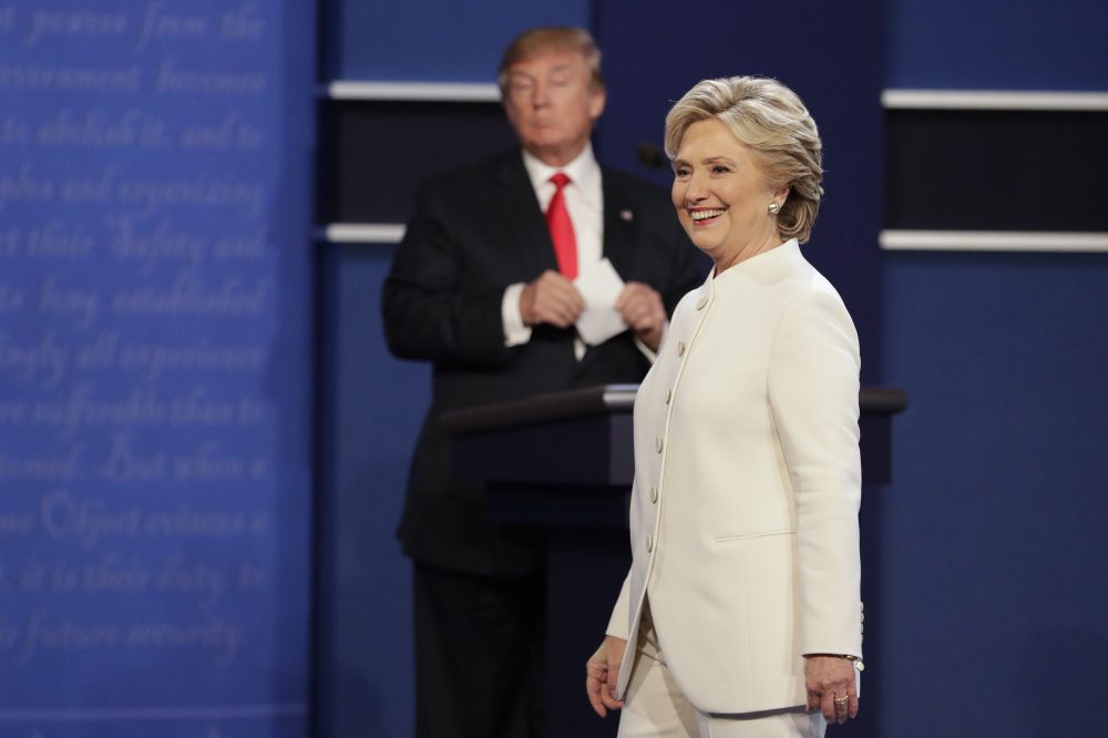 Hillary Clinton walks toward the audience as Donald Trump stands behind his podium after the third presidential debate, Oct. 19, 2016. (John Locher/AP)