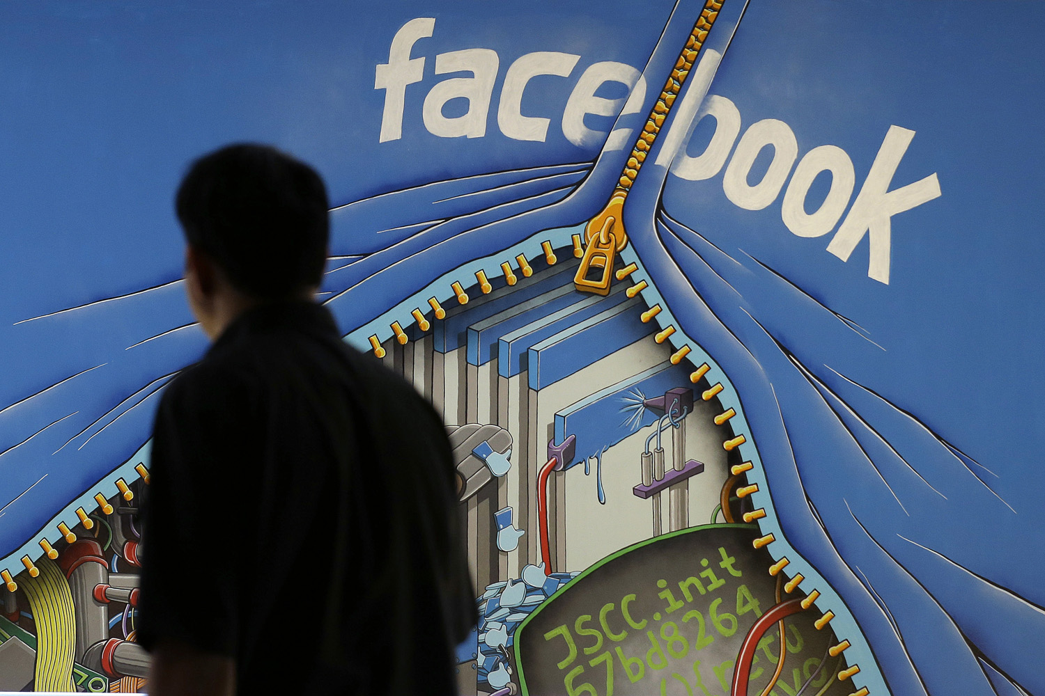 A man walks past a mural in an office on the Facebook campus in Menlo Park, California. (Jeff Chiu/AP)